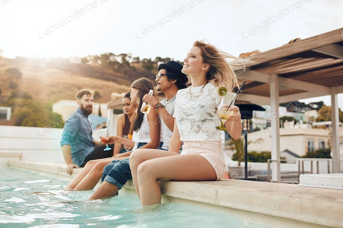 Friends partying by poolside