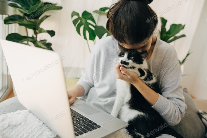 Casual girl hugging her cat and working on laptop, in modern room with pillows and plants