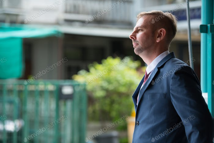 Portrait of businessman with blond hair waiting outdoors