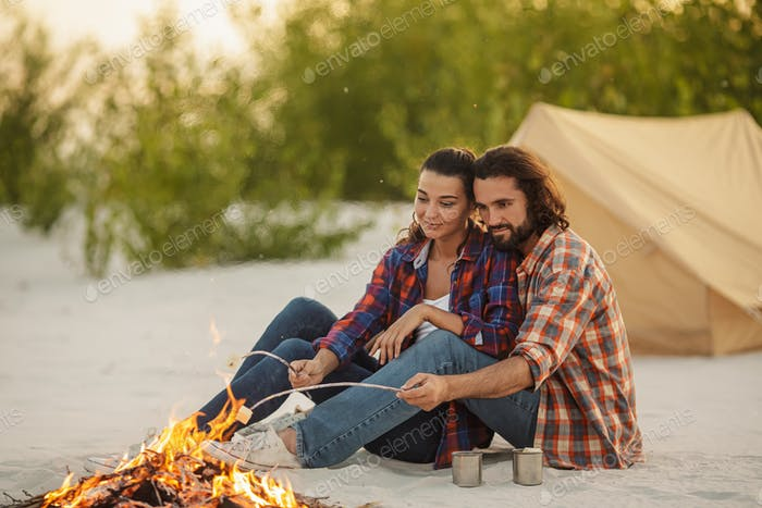 Couple Camping Near Campfire