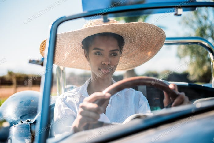 Black woman driving a vintage convertible car