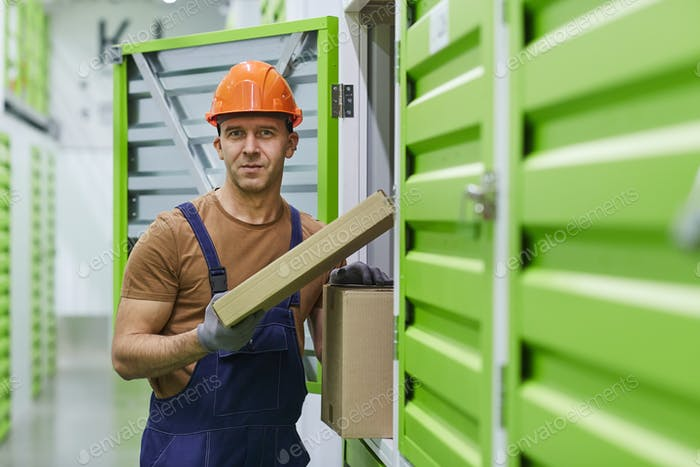 Worker with parcels in warehouse