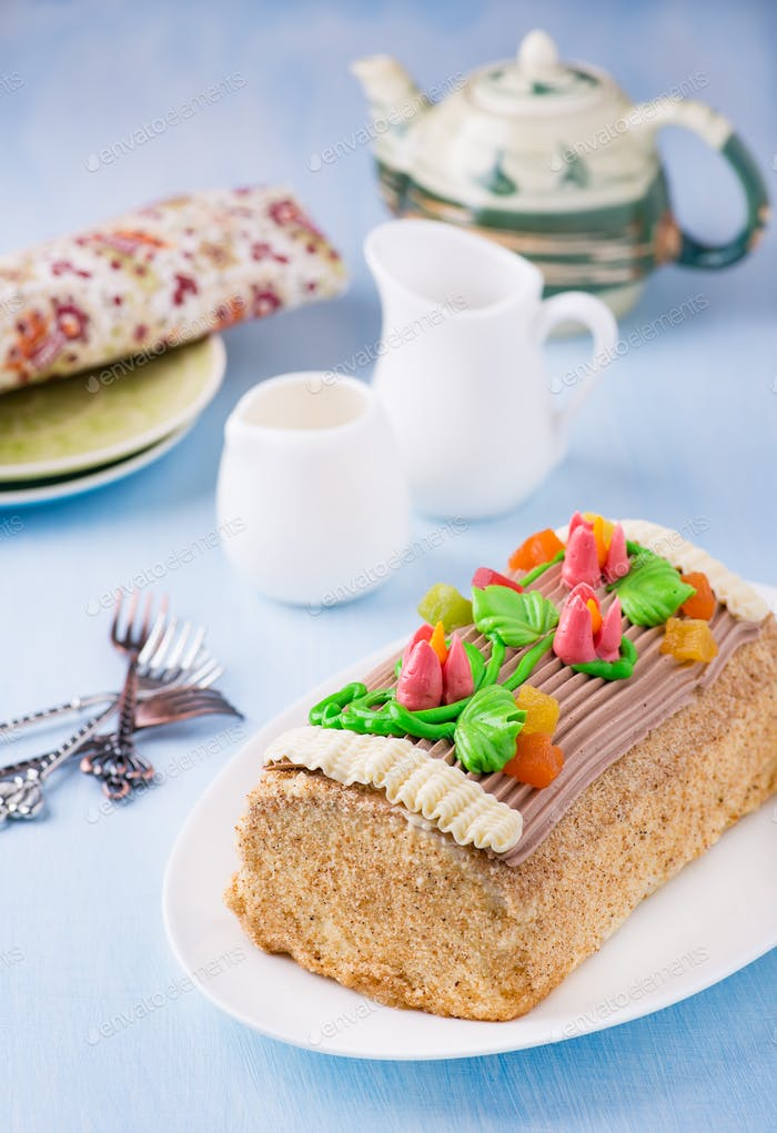 Roulade cake, decorated with colourful buttercream flowers