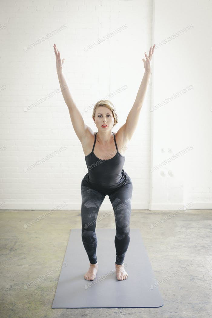A blonde woman doing yoga squatting down with her arms raised.