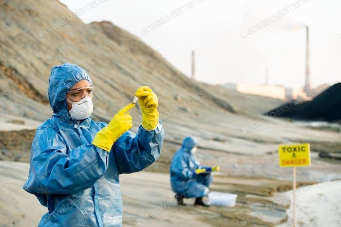 Forscher in Schutzanzüge Blick auf die Probe des toxischen Bodens in den Händen