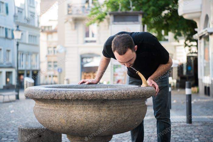 Hombre caucásico preparándose para beber agua de la fuente.