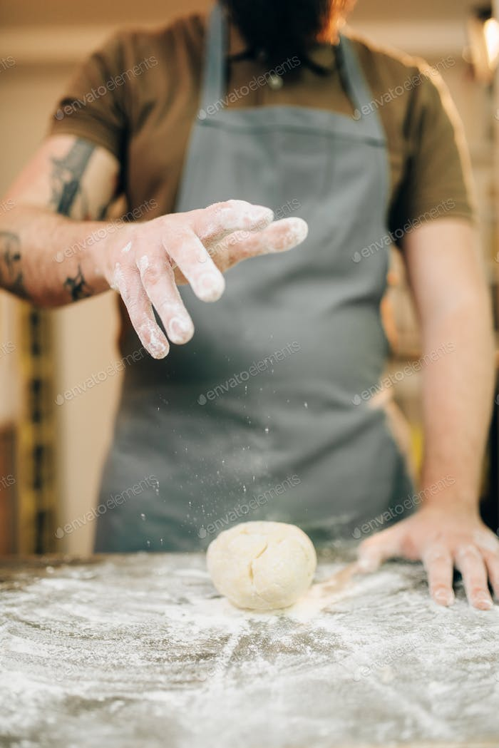 Fresh pasta cooking, chef in apron makes dough