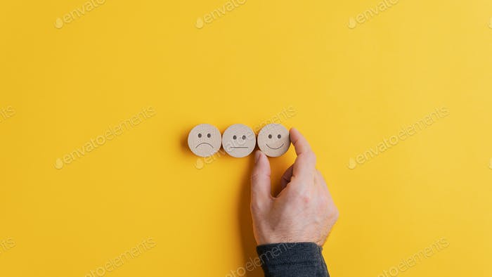 Male hand choosing a smiling face option from the row of three choices
