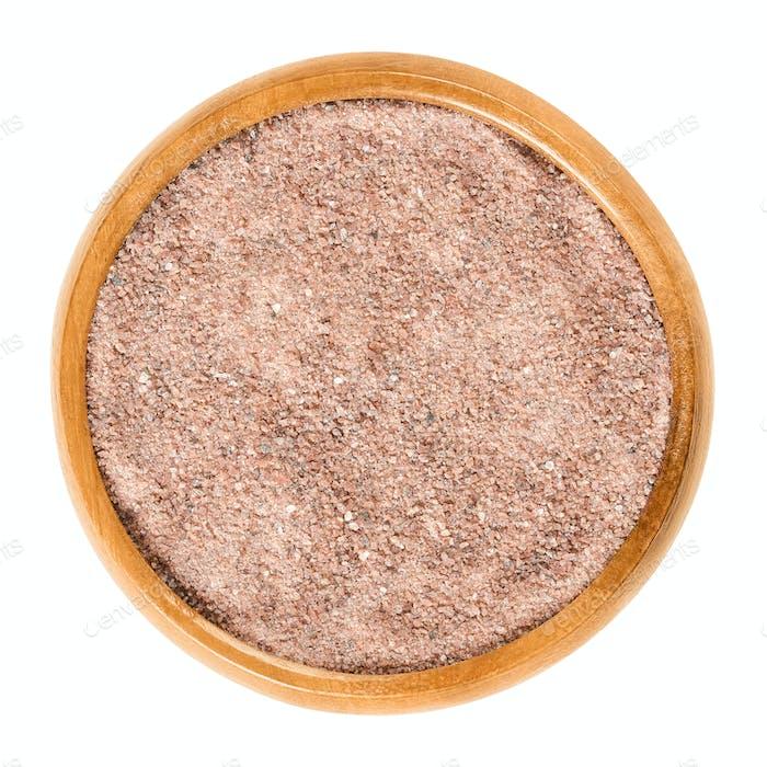 Kala Namak salt powder in wooden bowl over white