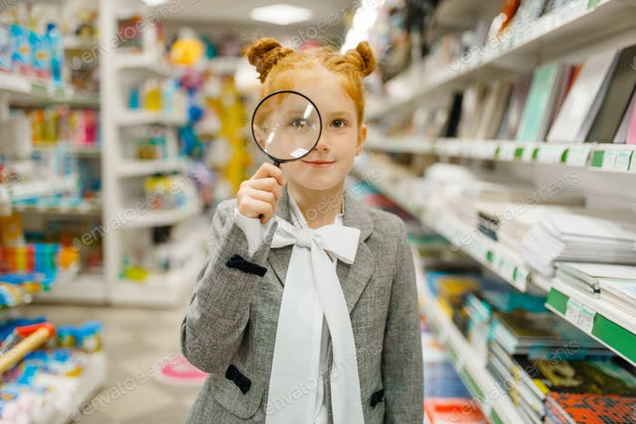 Schoolgirl choosing magnifying glass, stationery