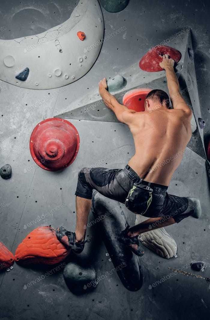 Man climbing on an indoor climbing wall.
