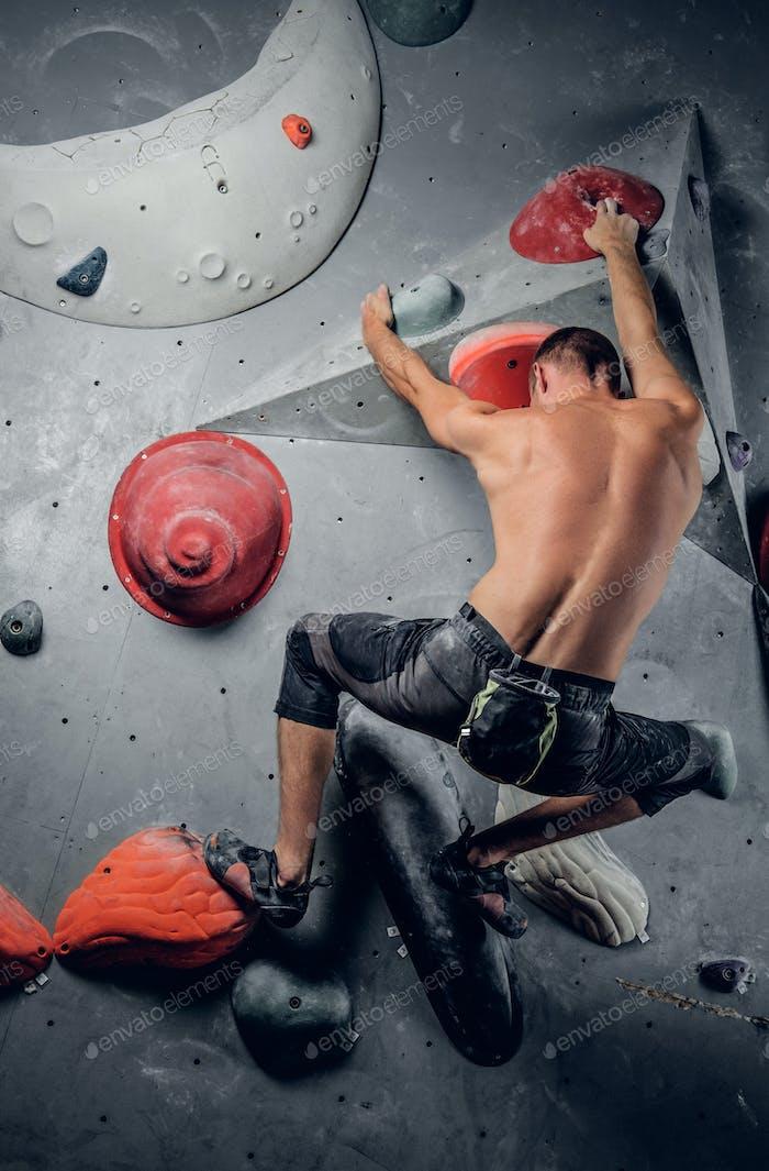 Man klettert auf einer Indoor-Kletterwand.