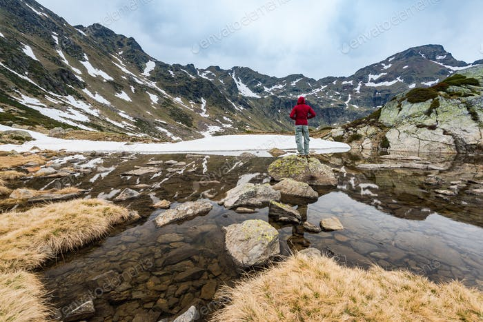 Hiker stands on rock near lake in Andorra