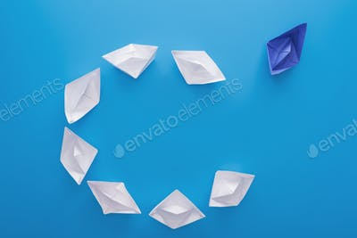 Flat lay with white and blue paper boats on blue