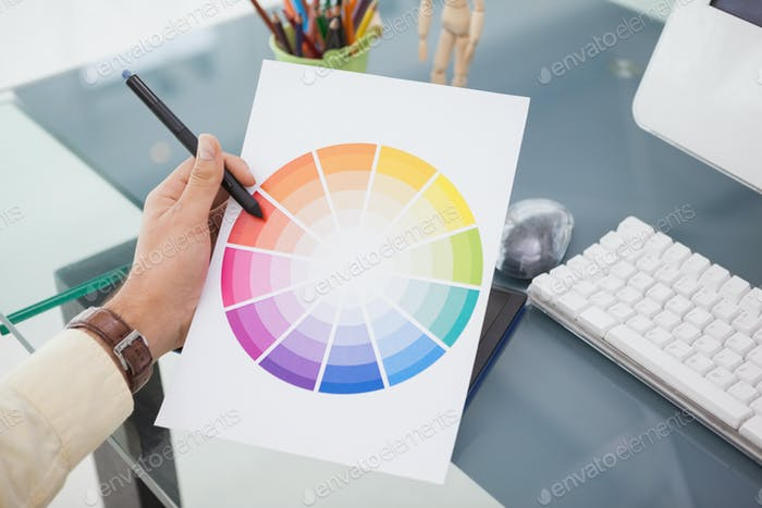 Designer working at desk using a colour wheel in his office
