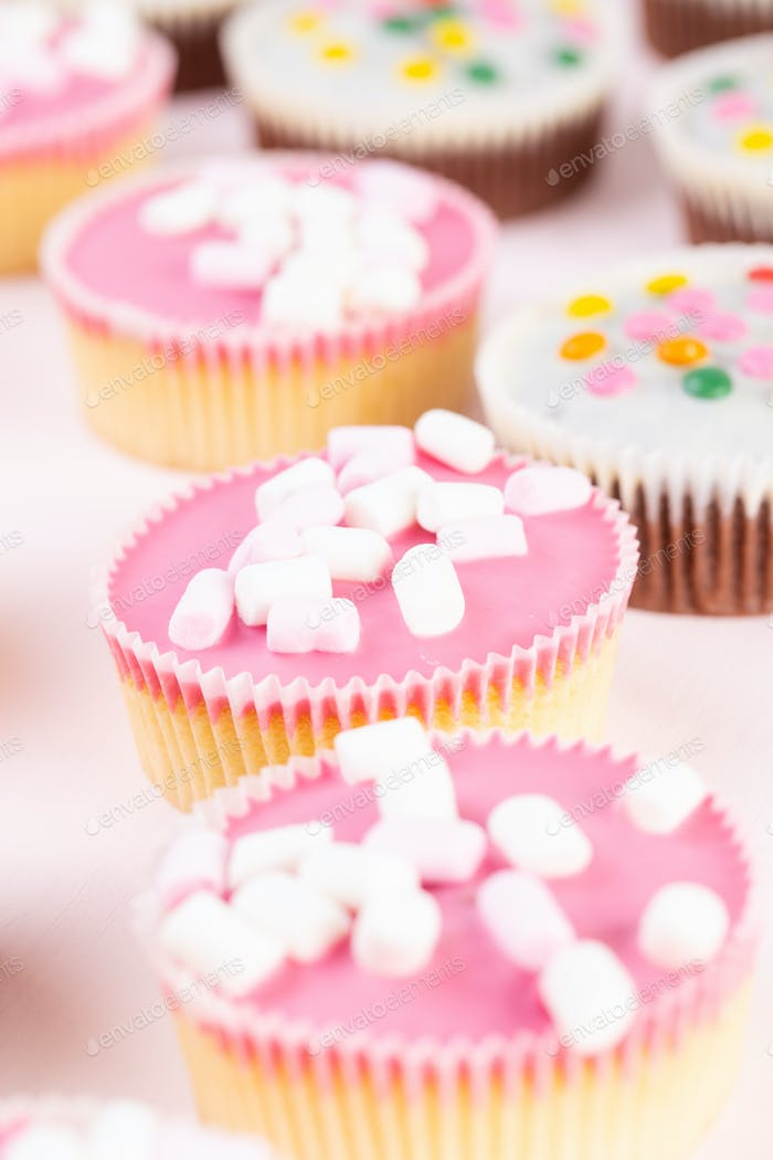 Colorful cupcakes on a pink background.
