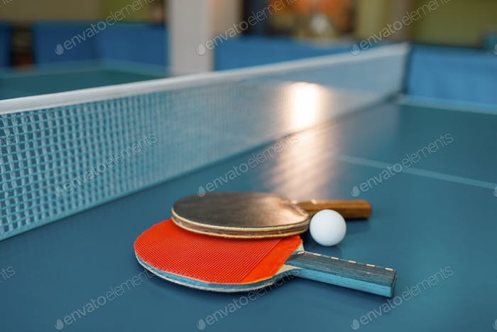 Two ping pong paddles on the table with net