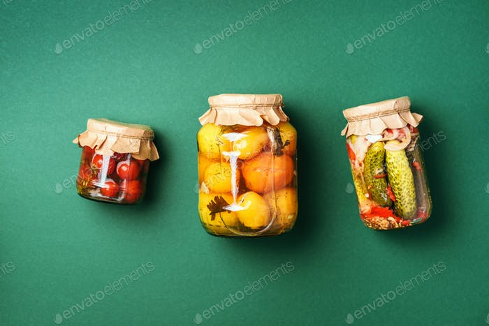 ?ucumber, squash and tomatoes pickling and canning into glass jars. Ingredients for vegetables