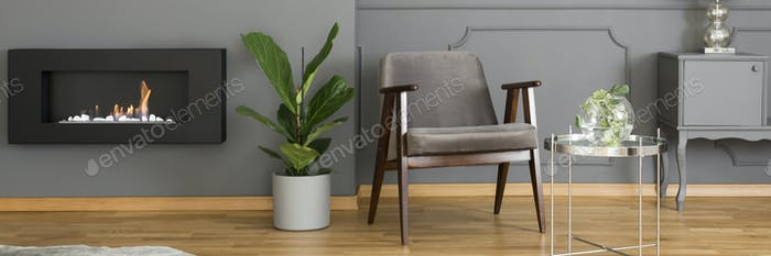 A silver side table and an elegant, upholstered armchair in a mo