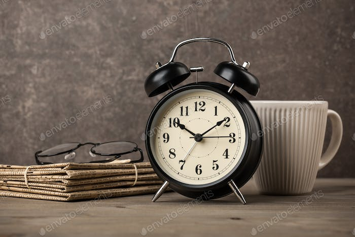 Newspapers, glasses, alarm clock and coffee cup on desktop