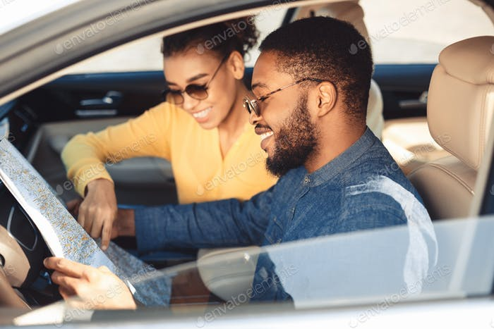 Happy black couple looking at map in car