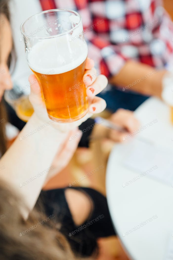 Woman holding glass of beer