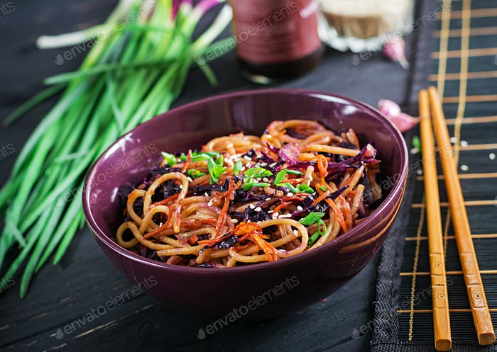 Chinese food. Vegan stir fry noodles with red cabbage and carrot in a bowl