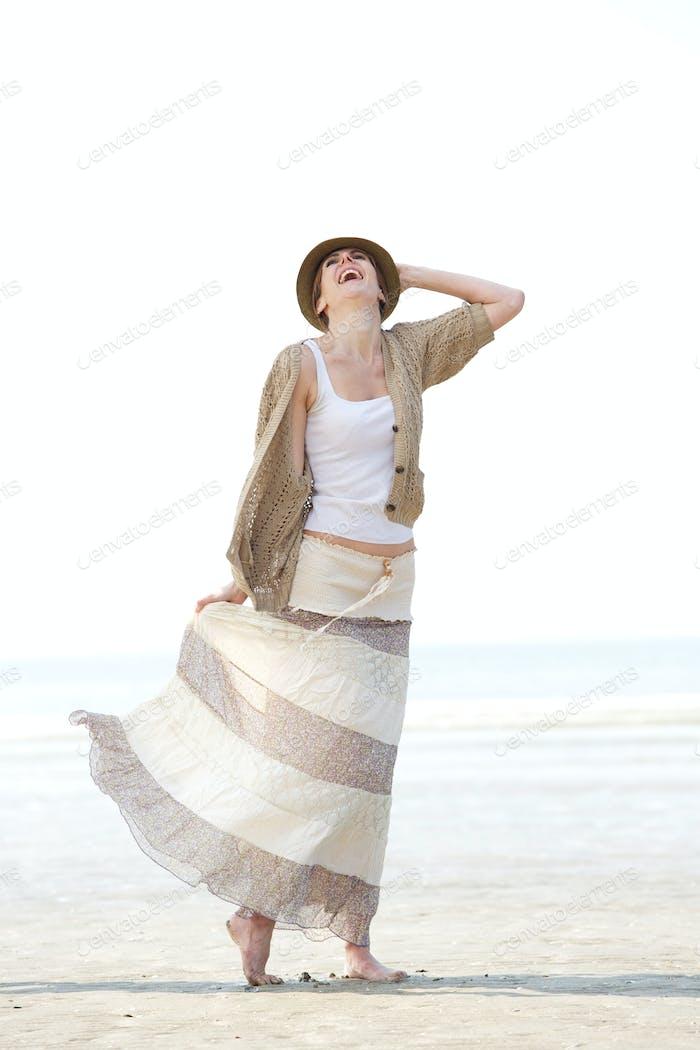 Cheerful woman walking on the beach