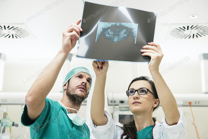 Medicine doctor showing something to her male colleague on x-ray image.