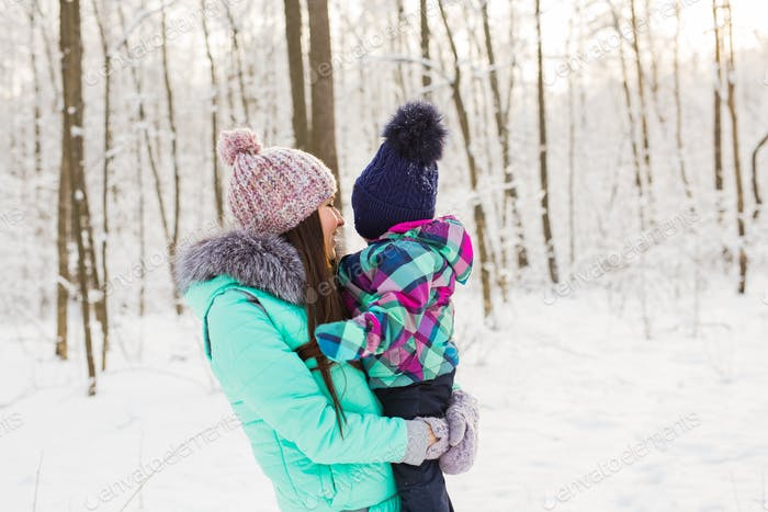 Thumbnail for happy mother holding baby girl on the walk in winter snowy forest