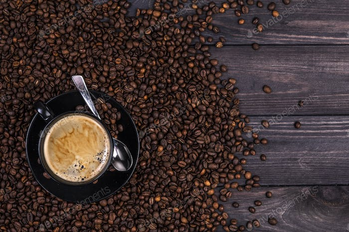 Coffee background, top view with copy space. Coffee cup and coffee beans on black wooden background