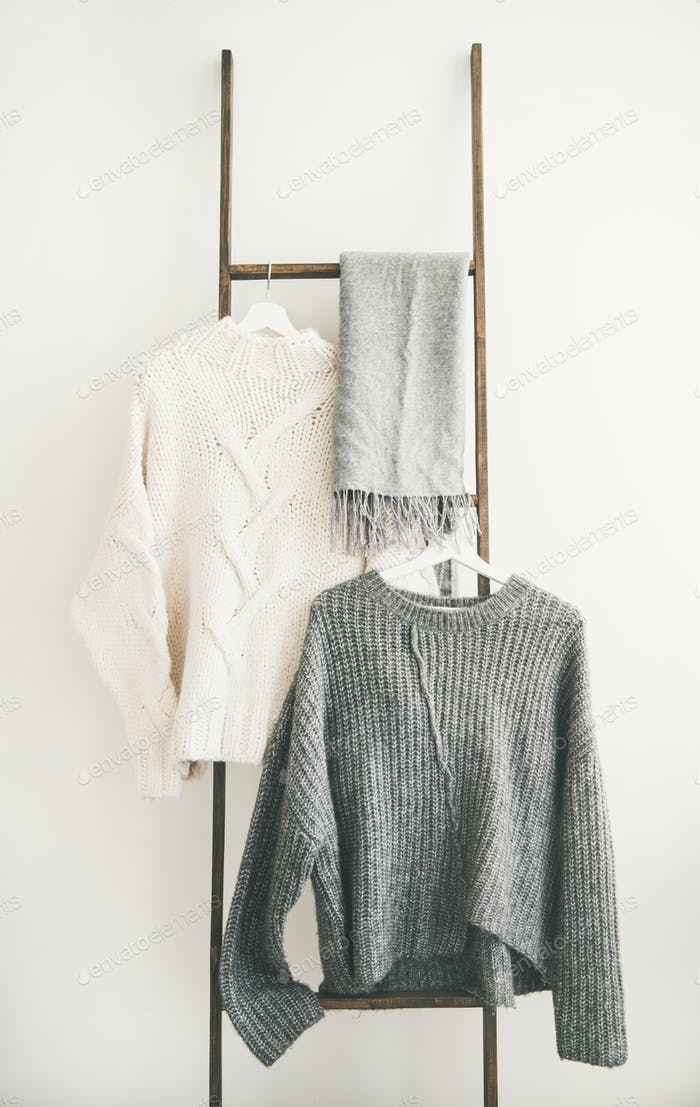 Fall or winter warm sweaters on hanger and winter boots