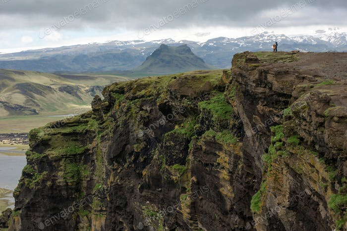 Icelandic landscape with volcanic lava ridge, glacier mountains, green grass. Vik area, Iceland