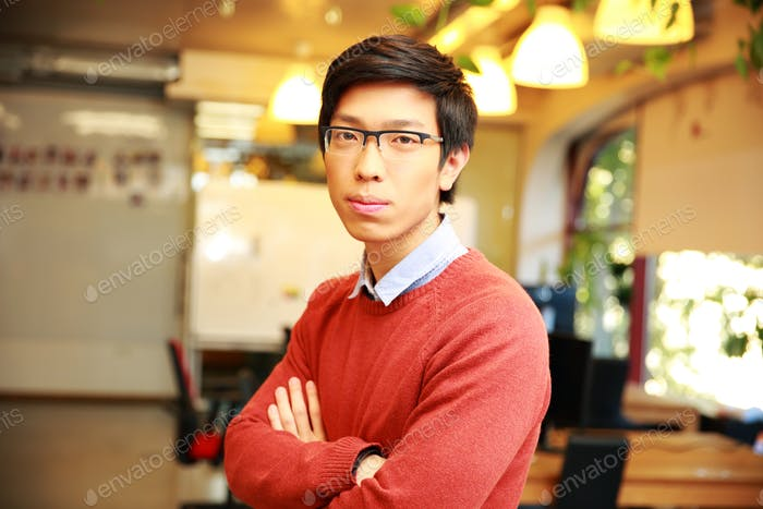Young thoughtful asian male student with arms folded standing in classroom