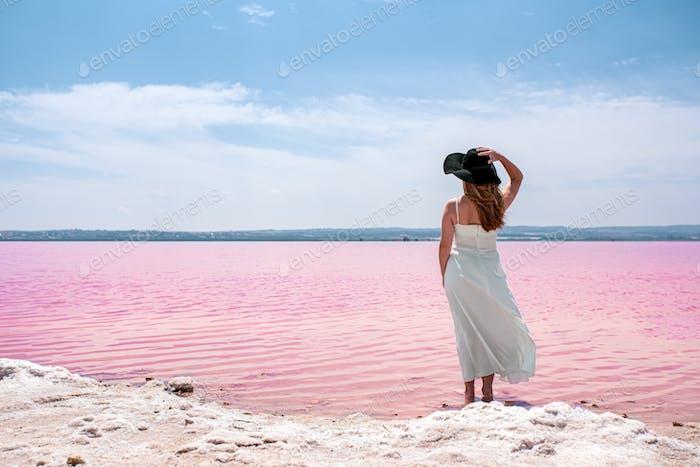 Rückansicht der niedlichen teenager Frau tragen weißes Kleid zu Fuß auf einem erstaunlichen rosa See