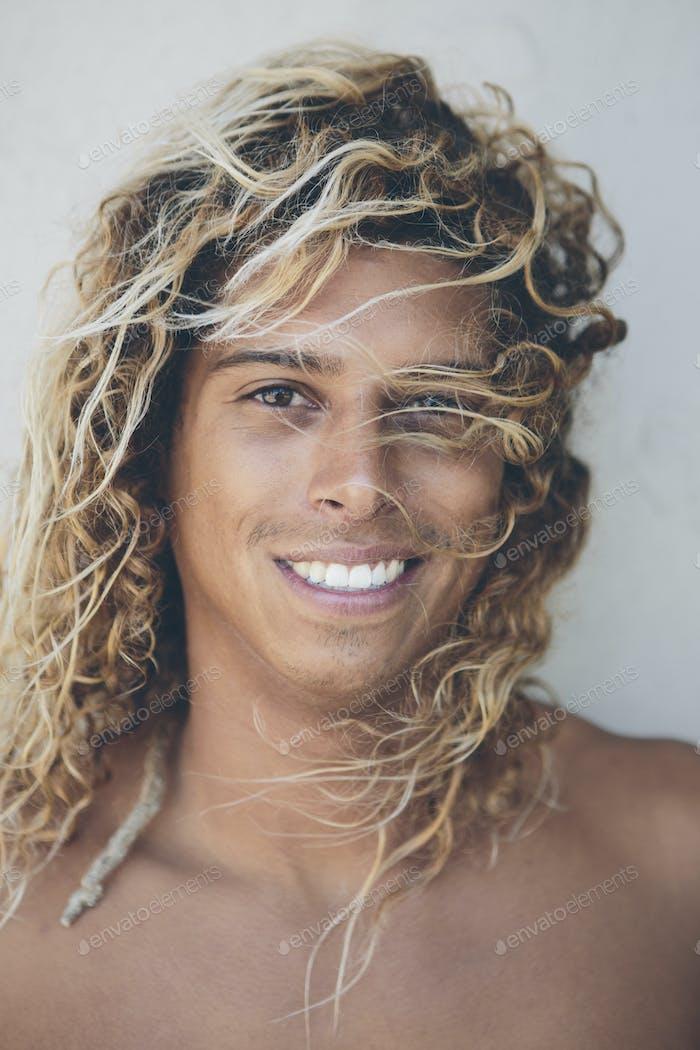 Retrato de joven surfista hispano con cabello rubio blanqueado.
