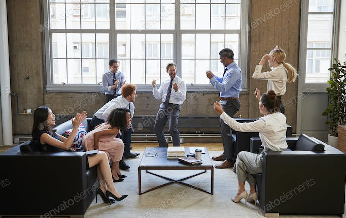 Business team celebrate hitting target at informal meeting
