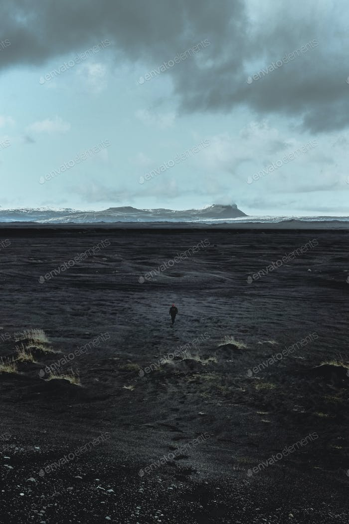 Man walking to a far away mountain on the black sands