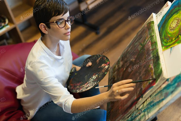Creative pensive art school painter working on painting