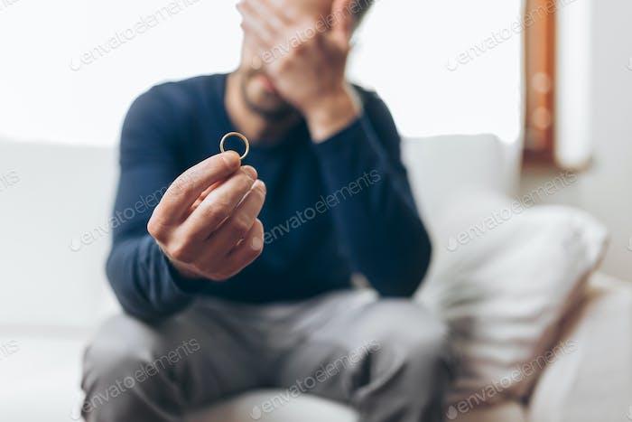 Heartbroken Mann hält einen Ehering