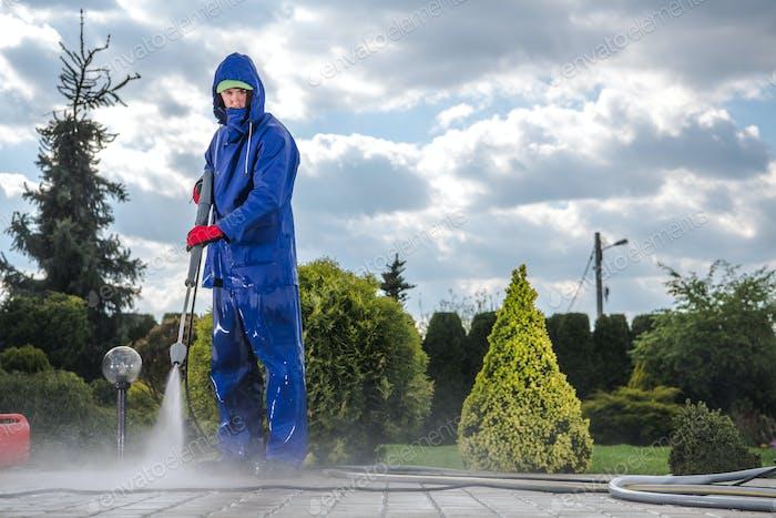 Männliche Groundkeeper Reinigung Bürgersteig Mit Hochdruck-Ausrüstung.