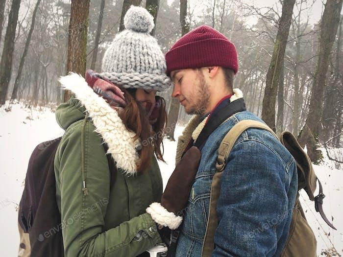 Happy Hipster Paar in stilvollen Outfits umarmen und küssen im verschneiten Winterpark
