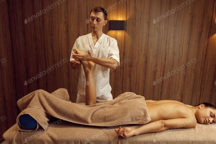 Male masseur stretching legs to young woman