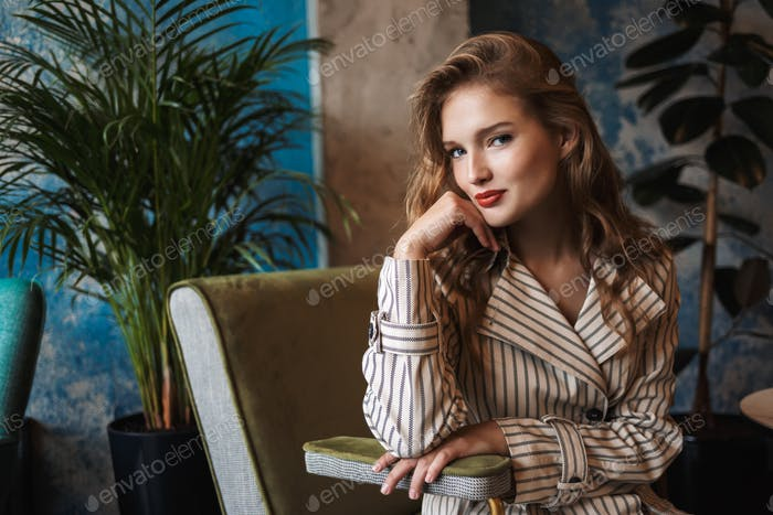 Young attractive lady with wavy hair in striped trench coat play