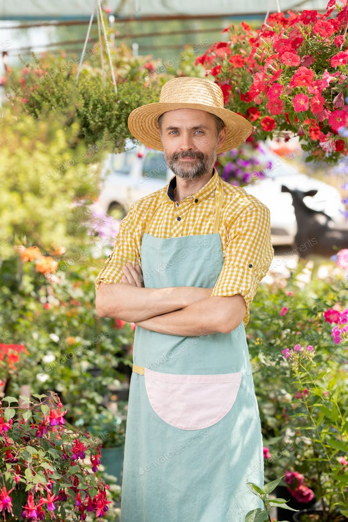 Mature male farmer or gardener in apron and hat standing in greenhouse