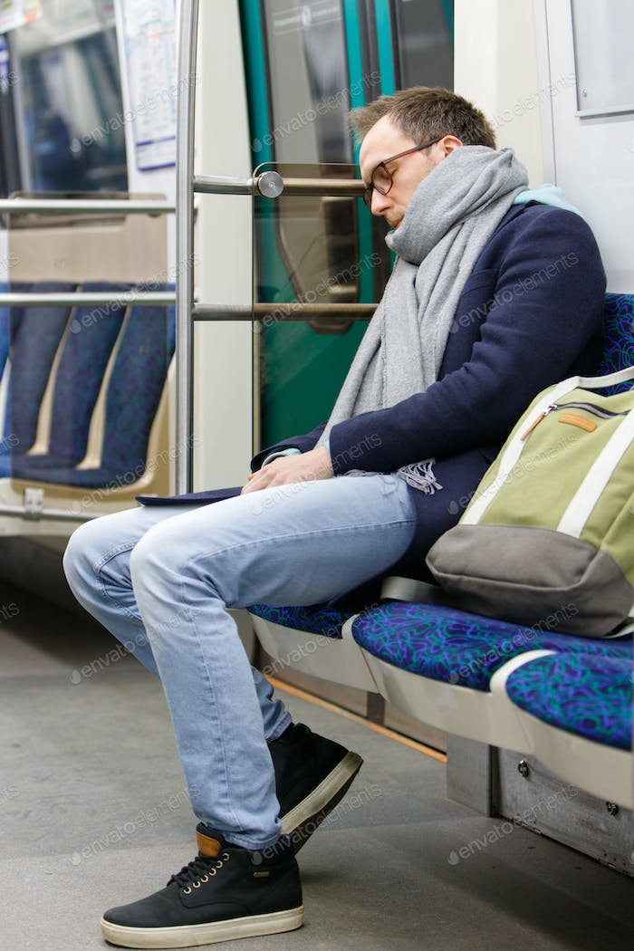 Exhausted man sleeping in subway train after work. Chronic fatigue, sleep deprivation concept