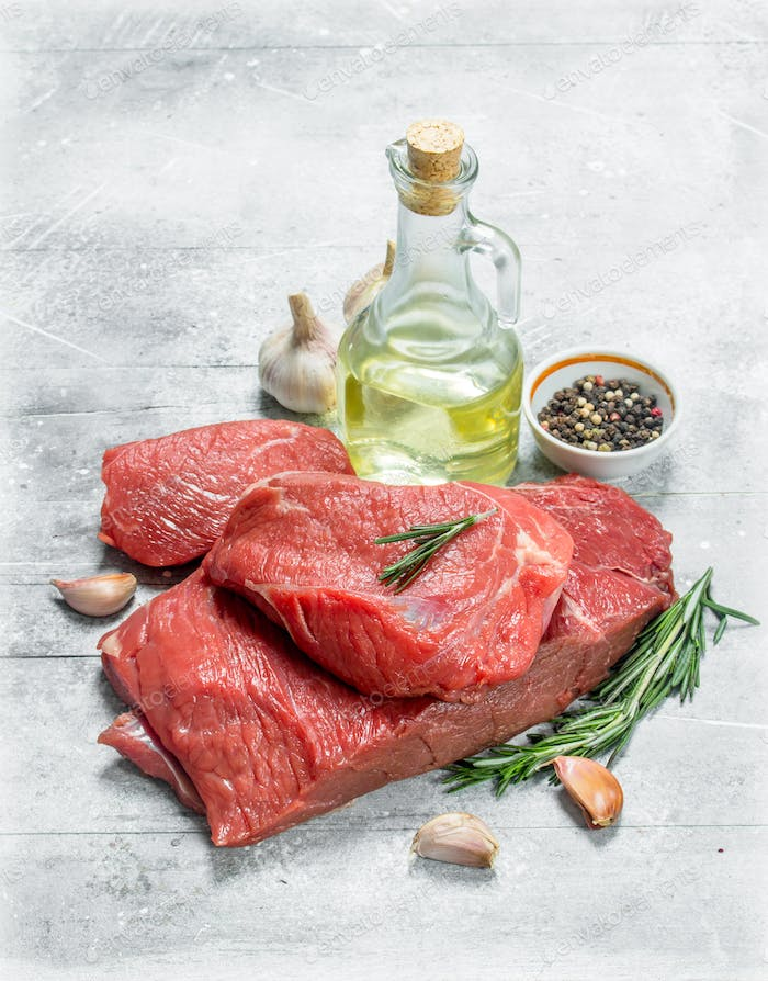 Raw meat.Pieces of beef with garlic, rosemary and olive oil.