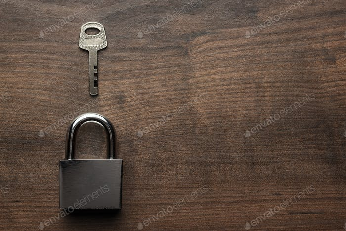 Check-Lock And Key On The Brown Wooden Table