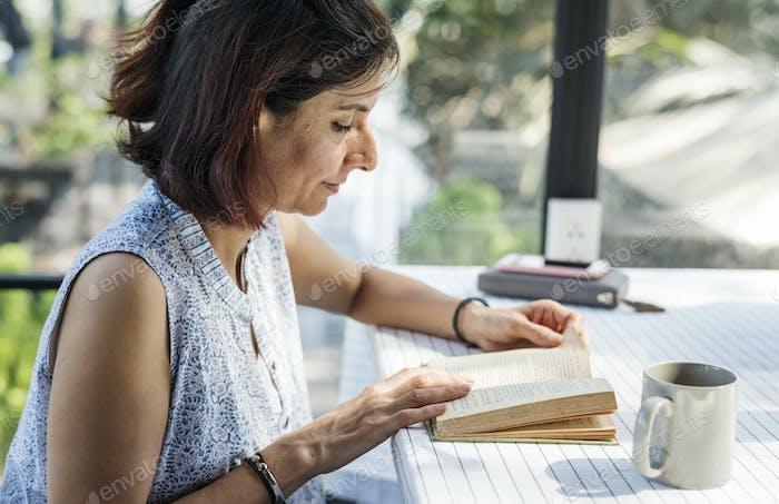 Frau liest ein Buch in einem Café im Freien