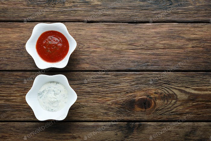 Ketchup with mayonnaise sauces at wood, top view.